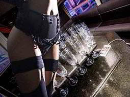 An image of champagne flutes inside a party bus overlaid with a woman's body wearing black lingerie