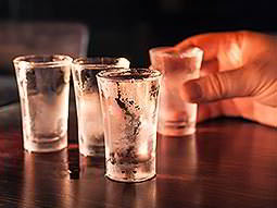Four shot glasses on a wooden surface, one being held by a hand