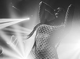 Black and white image of a woman in a fishnet top