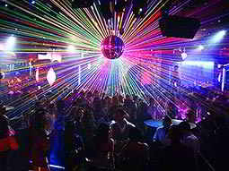 People dancing in a club to a backdrop of lights from a disco ball