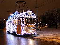 A tram covered in white lights driving down an icy street