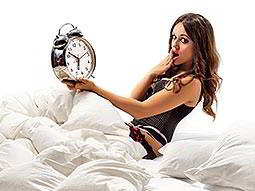 A woman lying in bed, holding a large alarm clock and posing with her hand over her mouth