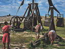 An old wooden trebuchet being operated by three people