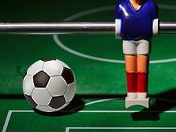 A close up of a traditional table football player and ball