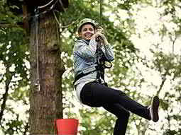 A woman wearing a helmet hanging from a rope attached to a harness