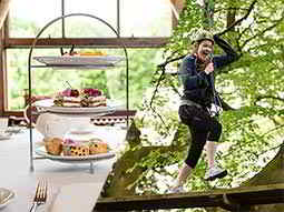 A split image of a cake stand filled with cakes and a woman running along a wooden board in a helmet and harness
