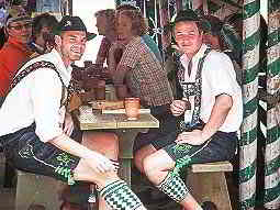 Two men in lederhosen costumes, sat at a table and drinking beer with people sat in the background