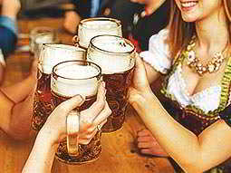 Peoples hands toasting with full steins on a table