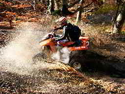 A quad bike driving through muddy water in a forest