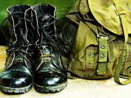Close up of a pair of black army boots next to a green rucksack