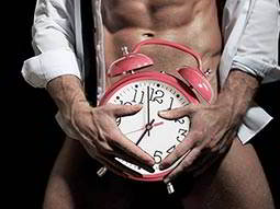 A man wearing only an unbuttoned shirt holding an alarm clock over his groin