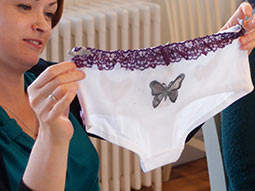 Several pairs of white knickers featuring different designs, on a table