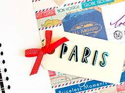 A paris tag with a red ribbon, on top of a colourful scrap book