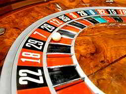 Close up of a white ball in red seven on a roulette wheel