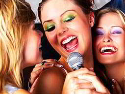 Three girls singing into a microphone together