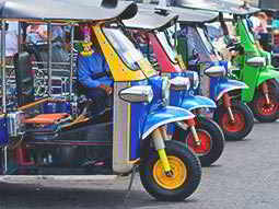A line of colourful, parked-up tuk tuks
