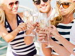 Two women and a man toasting with champagne flutes on the deck of a boat