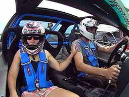 A man and a woman sitting in the front seats of a racing car wearing helmets and harnesses