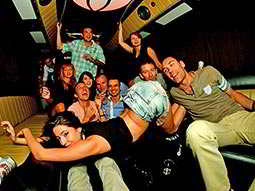 Group of men and women posing in a party bus