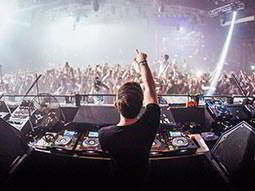 The back of a DJ in a booth, with his hand up to the crowd
