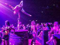 A man balancing on a barrel and performing to a crowd, to a backdrop of purple light