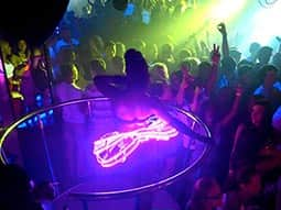 A woman dancing in a circle-style cage in a club, with people dancing around her