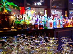 The stems of upside down glasses on a bar, with spirit bottles in the background