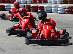 Three go karts racing against each other on an outdoor track
