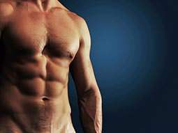 A naked mans torso with defined abs