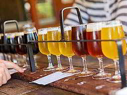 Five different beers lined up in glasses, within a wooden sampler plank