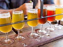 A wooden rack of six craft beers on a table