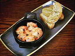 A plate with a bowl of prawns and some pieces of bread on