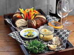 Food and sauces served up on a wooden board, next to wine glasses