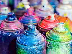 The tops of coloured spray paint cans