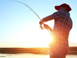 A man catching a fish at sunrise