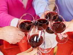 Five people holding glasses with red wine in, in a cheers position
