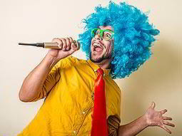 A man in a blue wig, green glasses, a yellow shirt and red tie singing into a microphone