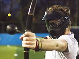 A split image of a man with a paintball splatter on his visor, and a man firing a bow and arrow at a target
