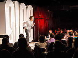 A person performing stand up comedy on stage at Glee club