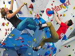 A split image, one of a man and a woman climbing separate climbing walls