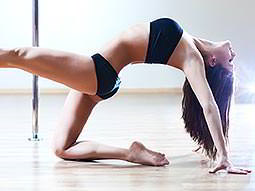 A woman in black underwear stretching on the floor in front of a metal pole