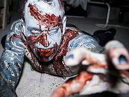 A man dressed up as a zombie and reaching for the camera