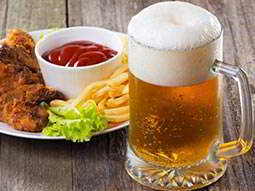 A plate of food and a tankard-style glass of beer