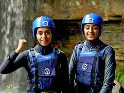 Two women wearing blue life vests and helmets