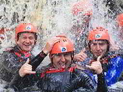 Three men posing under a waterfall wearing orange helmets