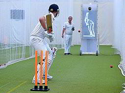 A man holding a bat and preparing to hit a ball in front of orange wickets
