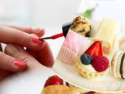 A split image of a womans nails being painted and a high tea being displayed