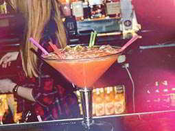 A giant sharing cocktail on the bar with many straws poking out