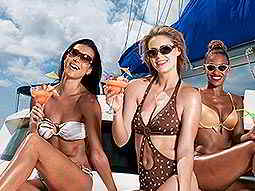 Three women wearing bikinis and sunglasses, on the deck of a boat