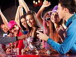 A mixed group of party goers being served drinks at a bar
